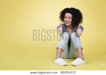 Success concept with woman: Successful happy woman with thumbs up being excited on isolated yellow background with empty copy space.