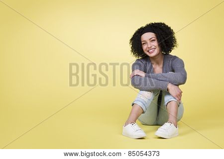 Joyful smiling woman sitting on yellow isolated background with empty copy space.