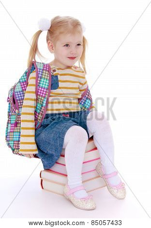 charming little schoolgirl with satchel behind him sitting on a