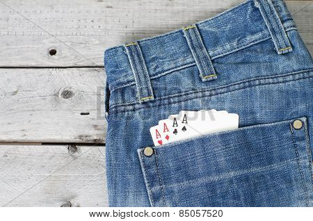 Four Aces In Blue Jeans Back Pocket Against Wooden Background
