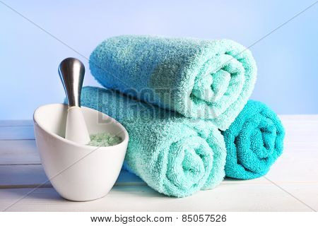 Rolled towels with sea salt on wooden table and light colorful background
