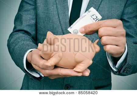 closeup of a young man wearing a suit introducing a pound sterling bill in a piggy bank