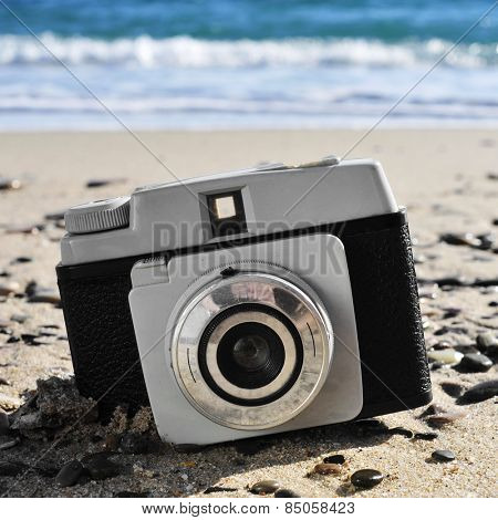 closeup of a an old camera on the sand of a beach