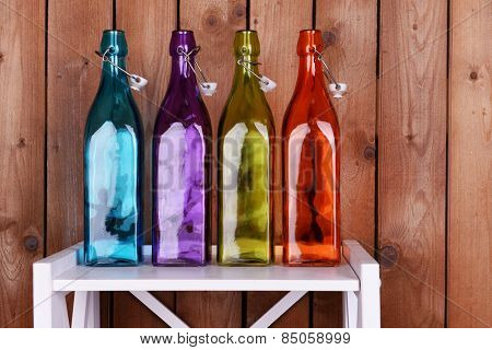 Interior design with colorful glass bottles on tabletop on wooden planks background