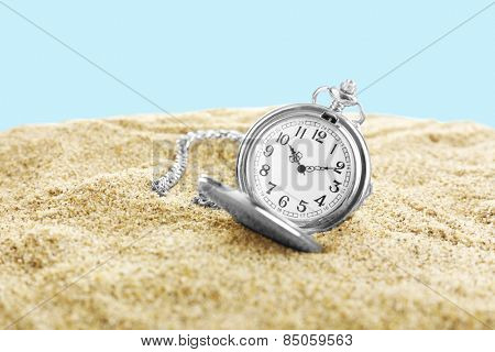 Silver pocket clock on sand on blue background