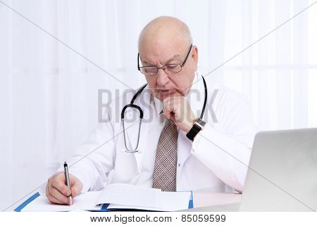 Portrait of professional doctor at table in his office on white curtain background