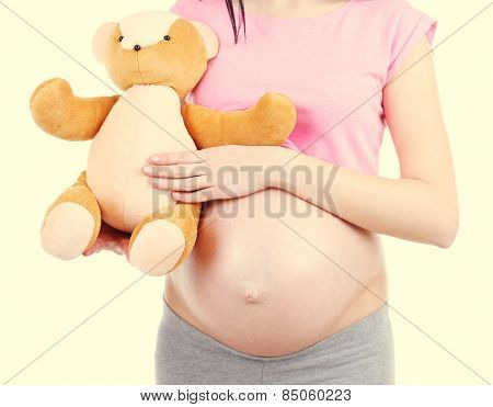 Beautiful young pregnant with baby toy on light background