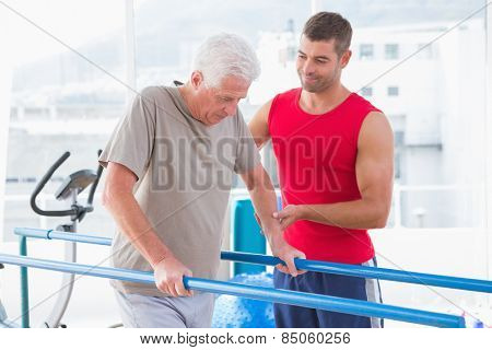 Senior man walking with coach help in fitness studio
