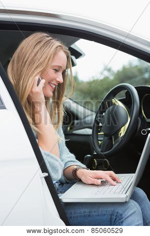 Young woman working in the drivers seat in her car