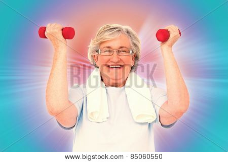 Senior woman lifting hand weights against abstract background