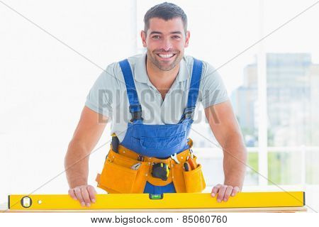 Portrait of smiling handyman using spirit level in bright office