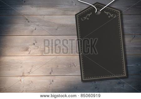 Elegant dark grey tag against bleached wooden planks background