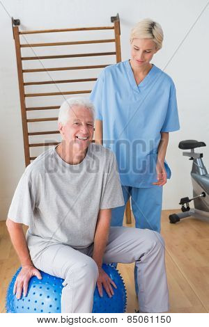 Smiling senior man with his therapist in fitness studio