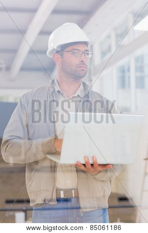 Male architect wearing hardhat while using laptop in office