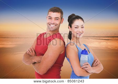 Fit man and woman smiling at camera together against hazy blue sky
