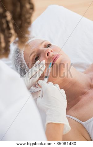 Woman receiving botox injection on her lips in medical office