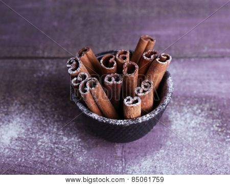 Cinnamon sticks in small bowl with powdered sugar on color wooden table background