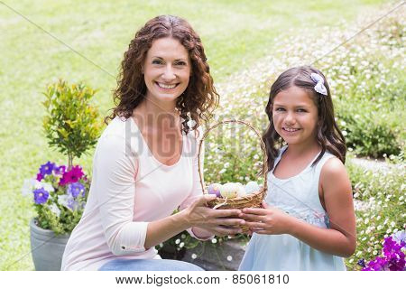 Happy mother and daughter collecting easter eggs in the garden