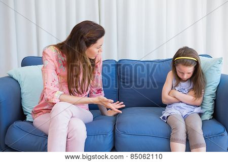 Mother scolding her naughty daughter at home in the living room