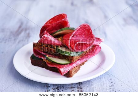 Sandwich with salami and cucumber on plate on color wooden table background