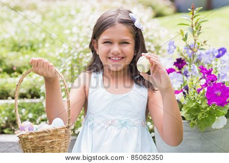 Happy girl collecting easter eggs in the garden