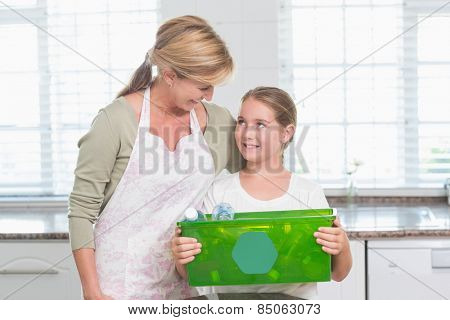 Daughter holding recycling box with her mother at home in the kitchen