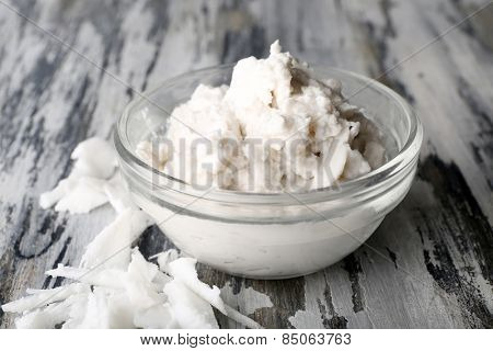 Coconut oil in bowl and coconut flakes on wooden background