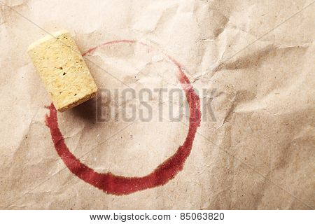 Wine stain and cork on crumpled paper background