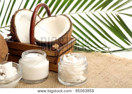 Coconut with jars of coconut oil and  cosmetic cream on sackcloth on natural background