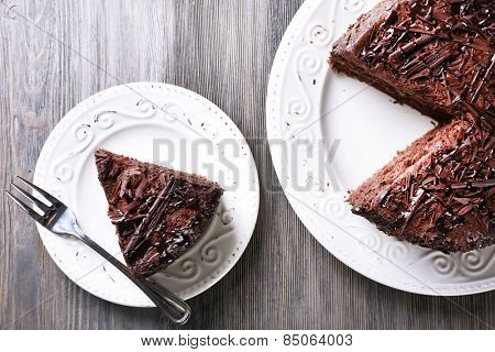 Sliced tasty chocolate cake on wooden table background