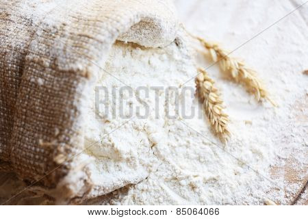 Flour in burlap bag on wooden cutting board background