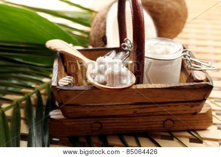 Jar of coconut oil with coconut and leaves on table close up