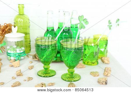 Composition for St Patrick Day with sweets and drinks on table on brick wall background