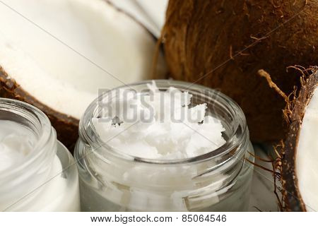 Coconut with jars of coconut oil and cosmetic cream close up