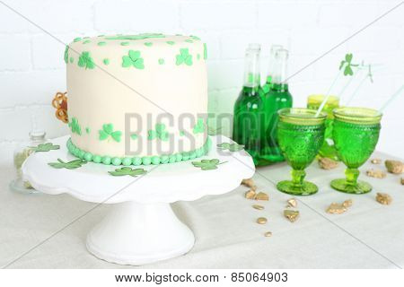 Tasty cake for St Patrick Day with drinks on table on brick wall background