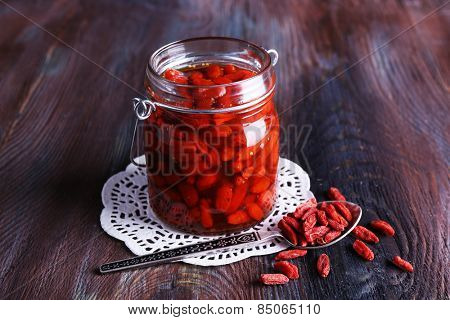 Goji berries in glass bottle on lace doily with silver spoon on rustic wooden table background