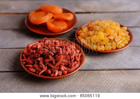 Dried fruits in small plates on wooden planks background