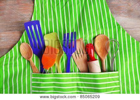 Set of kitchen utensils in pocket of apron, closeup