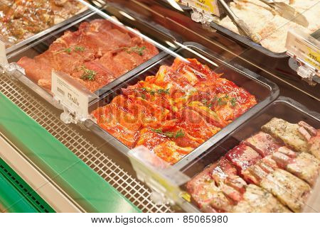 Meats in marinade on supermarket display, pre-cooked food