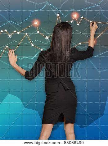 Business woman draws felt pen line graphs on the virtual wall