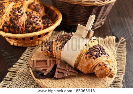 Fresh and tasty croissants with chocolate on wooden background