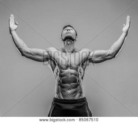 Portrait of a muscular man with raised hands up over gray background. HDR monochrome.