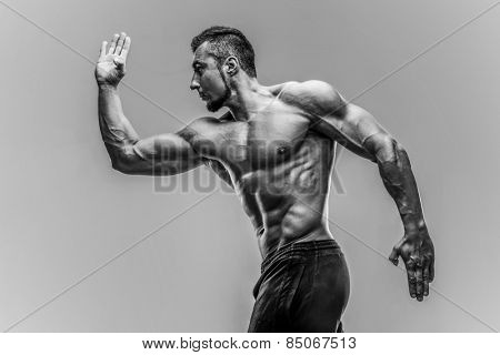 Portrait of a muscular man posing over gray background. HDR monochrome