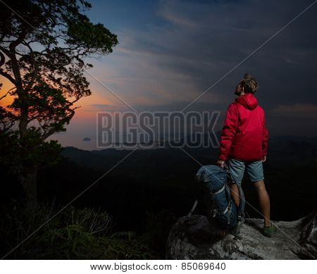 Young man hiker in red jacket standing on the rock and enjoying sunset over valley