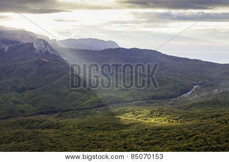 Ray of morning light over forest mountain slopes