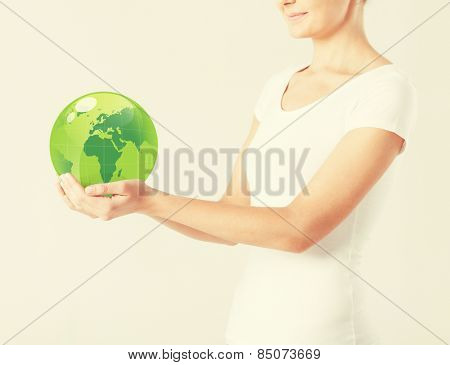 close up of woman holding green sphere globe