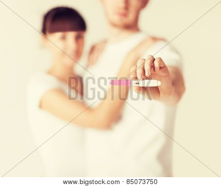 close up of woman and man hands with pregnancy test