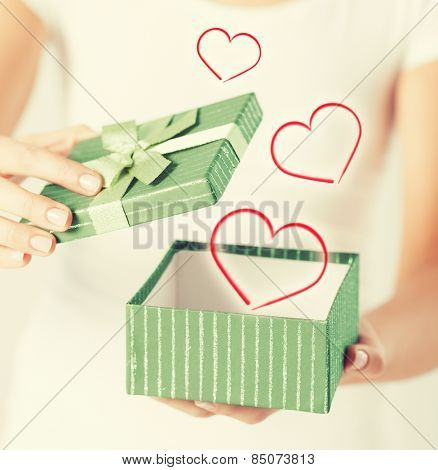 holidays and love concept - close up of woman hands opening gift box