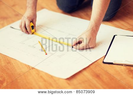 repair, building and home concept - close up of male hands measuring blueprint