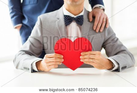 people, homosexuality, same-sex marriage, valentines day and love concept - close up of happy married male gay couple with red paper heart shape on wedding